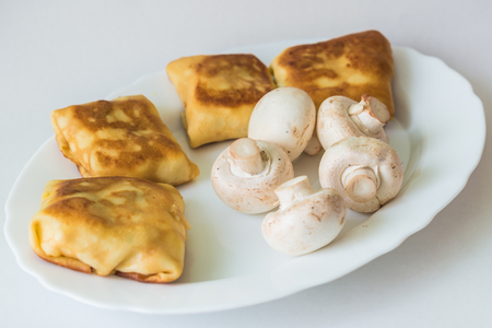 with fillings: Fried pancakes with fillings and mushrooms in the white plate on a white background Stock Photo