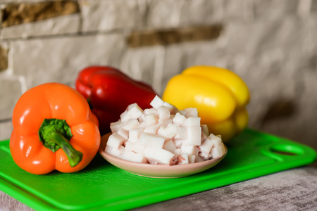 pancetta cubetti: Lard cubes in small plate with colored bell peppers on green plastic board