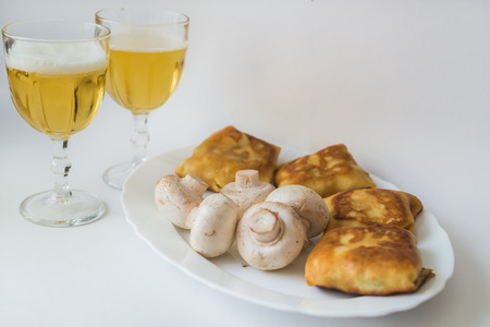 with fillings: Fried pancakes with fillings, mushrooms and glass of beer in the white plate on a white background Stock Photo