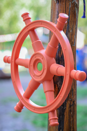 Red plastic childrens handlebar of the ship a wooden girder on the playground