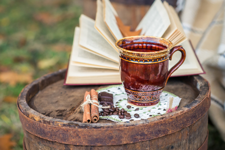 still life with cinnamon sticks, coffee beans and coffee cup on the old oak barrel in the garden autumn Stock Photo