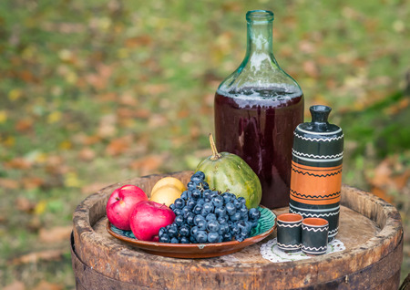 still life with oak barrel of fruit and red wine in the garden autumn Stock Photo