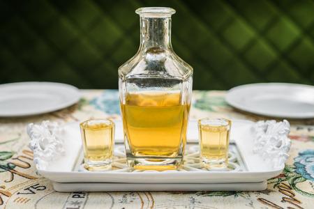 Karafka z miodem wódki na białym eleganckim tacy