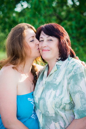 portrait daughter is kissing her mother on the cheek in the summer sunny day