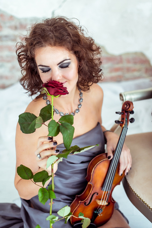 concerto: Beautiful woman holding a violin and smelling red rose
