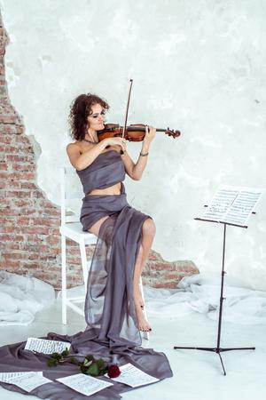 virtuoso: Beautiful woman playing the violin Stock Photo