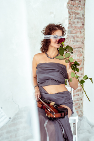 studioshoot: Beautiful woman holding a violin and smelling red rose