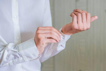 cufflink: Groom fastens a shirt