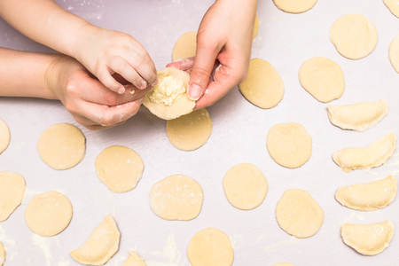 Mother and child hands make ravioli