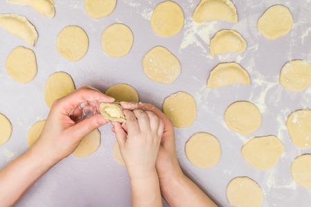 Mother and child hands make ravioli