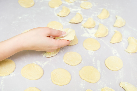 Side view womans hands make dumpling on table