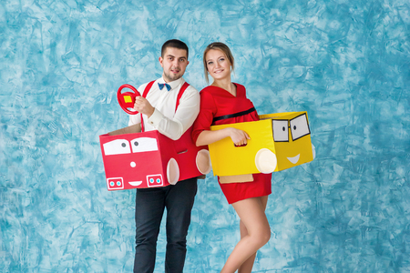Young couple moving in a toy cars
