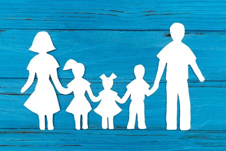 Closeup of happy paper family on blue background