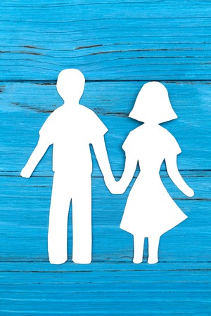 Paper silhouette of man and woman holding hands Stock Photo