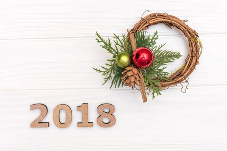 The numbers 2018 and wreath of pine branch and cone on white wooden background