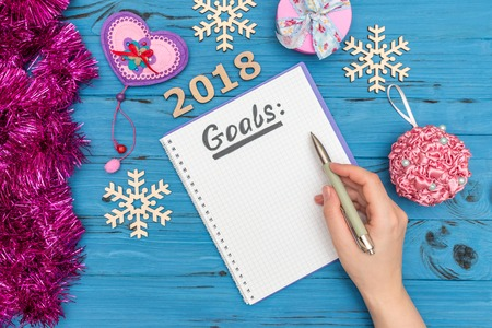 notebook with GOALS text and womans hand holding pen above with numbers 2018 and new year ornaments Banco de Imagens