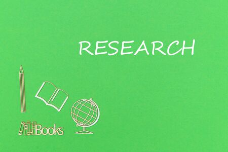 concept school for kids, text research, school supplies wooden miniatures on green backboard Stock Photo