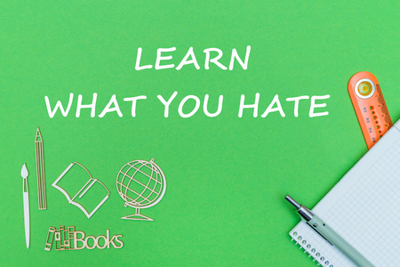 concept school, text learn what you hate, school supplies, notebook, ruler and pen on green backboard