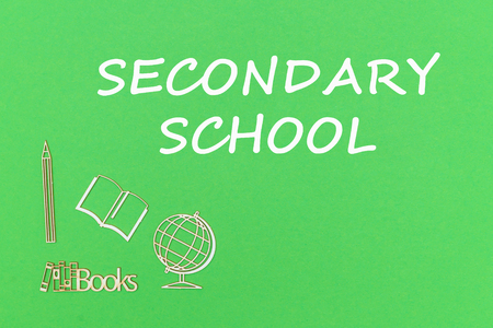 concept school for kids, text secondary school, school supplies wooden miniatures on green backboard