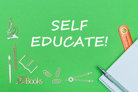 concept school, text self educate, school supplies wooden miniatures, notebook with ruler and pen on green backbord