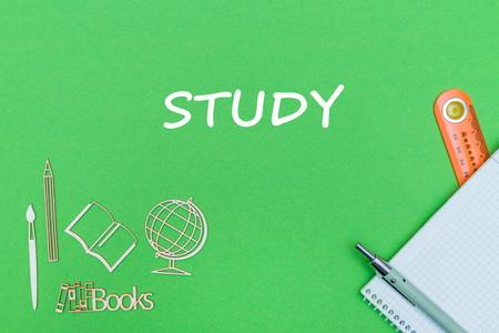 concept school, text study, school supplies, notebook, ruler and pen on green backboard