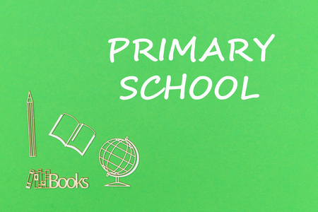 concept school for kids, text primary school, school supplies wooden miniatures on green backboard