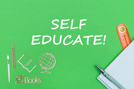 concept school, text self educate, school supplies, notebook, ruler and pen on green backboard