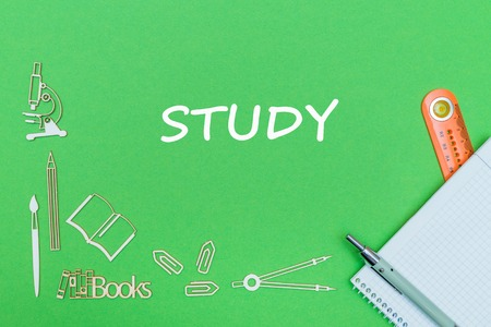 concept school, text study, school supplies wooden miniatures, notebook with ruler and pen on green backbord