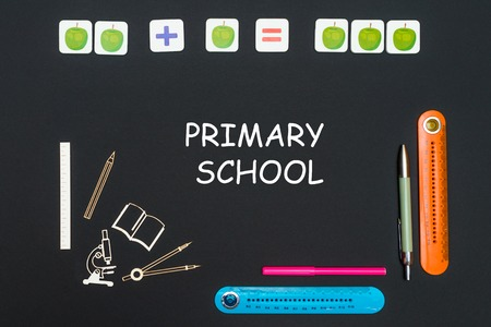 concept back to school, above stationery supplies and text primary school on black backboard Stock Photo