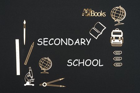 Concept back to school, text secondary school with school supplies chipboard miniatures placed on blackboard