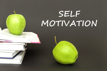 concept back to school, text self motivation, two green apples, open books on gray background