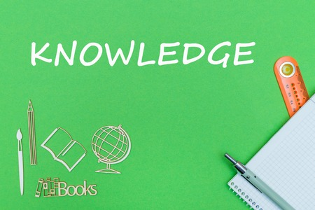 concept school, text knowledge, school supplies, notebook, ruler and pen on green backboard Stock Photo