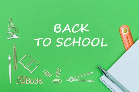 concept school, text back to school, school supplies wooden miniatures, notebook with ruler and pen on green backbord