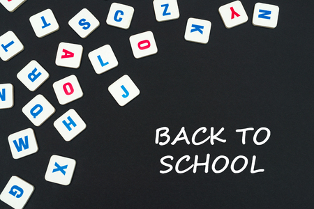 english school concept, text back to school, colored square english letters scattered on blackboard Stock Photo