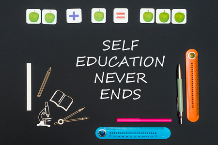 concept back to school, above stationery supplies and text self education never ends on black backboard