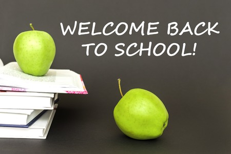 concept back to school, text welcome back to school, two green apples, open books on gray background Stock Photo