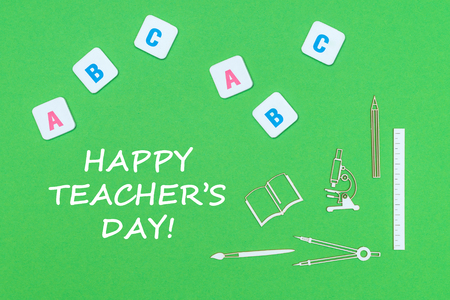 concept school, text happy teachers day, school supplies wooden minitures, abc letters on green backboard