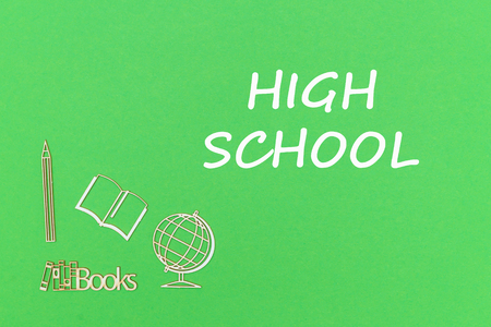 concept school for kids, text high school, school supplies wooden miniatures on green backboard
