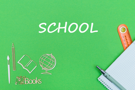 concept school, text school, school supplies, notebook, ruler and pen on green backboard