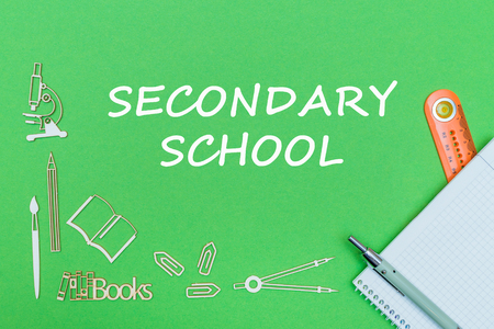 concept school, text secondary school, school supplies wooden miniatures, notebook with ruler and pen on green backbord