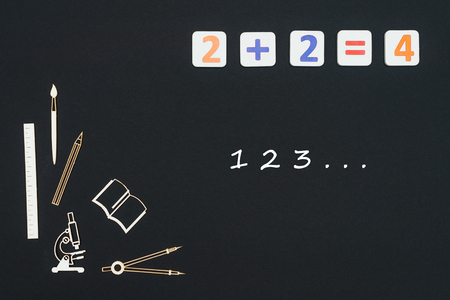Concept first class school, numbers 123 with wooden miniatures school supplies and elementary numbers on black background Stock Photo