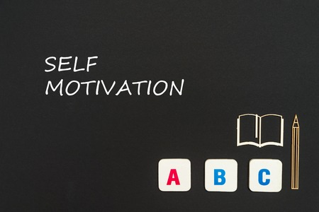 concept english school, text self motivation, abc letters, chipboard miniature book, pen on blackboard Stock Photo