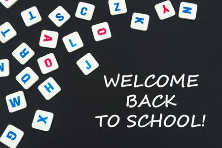 english school concept, text welcome back to school, colored square english letters scattered on blackboard Stock Photo
