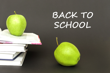 concept back to school, text back to school, two green apples, open books on gray background