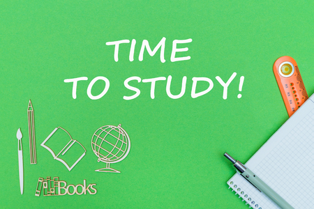 concept school, text time to study, school supplies, notebook, ruler and pen on green backboard Stock Photo