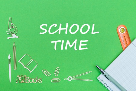 concept school, text school time, school supplies wooden miniatures, notebook with ruler and pen on green backbord