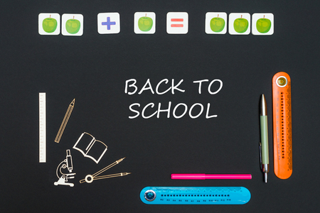 concept back to school, above stationery supplies and text back to school on black backboard