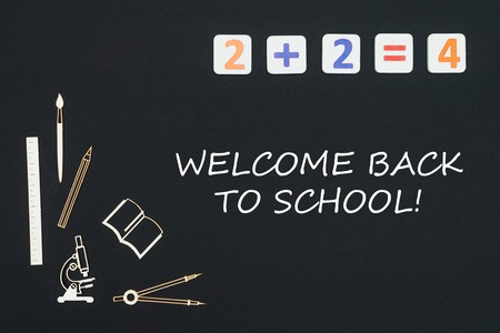 Concept first class school, text welcome back to school with wooden miniatures school supplies and elementary numbers on black background Stock Photo