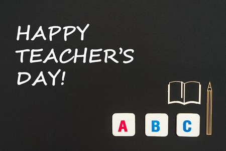 concept english school, text happy teachers day, abc letters, chipboard miniature book, pen on blackboard
