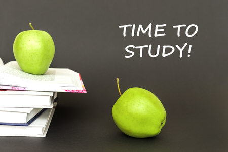 concept back to school, text time to study, two green apples, open books on gray background Stock Photo
